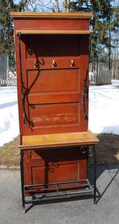 An antique five-panel door serves as the backdrop for this repurposed potting bench