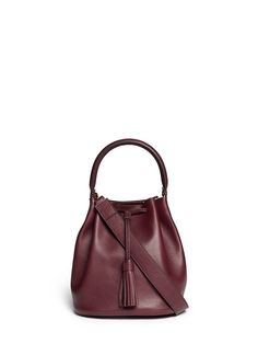 The season's highly sought-after bucket bag comes in a sumptuous shade of wine red in this compact version from Anya Hindmarch. Embodying the brand's elegant aesthetics,  this crossbody edition is fronted with a slender tassel that will complete your look with grace day or night.