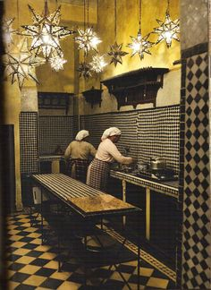 Women cooking in a black and white kitchen with Moravian starred ceiling