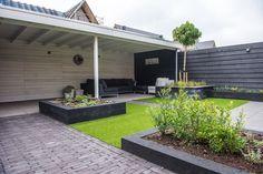 KernGroen realiseerde deze schitterende luxe tuin met veranda. Ook tijdens 'traditioneel Nederlands' zomerweer zit u hier nog gezellig buiten.