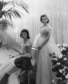 Jacqueline Bouvier, seated, with sister Caroline Lee Bouvier, in their debutante dresses.  1947.