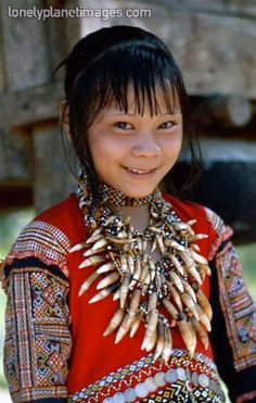 Philippines | Mansaka girl in traditional costume and jewellery of the region.This tribe is known for their use of coins in their decorations which can be seen used as a decorative motif on the top between the embroidery elements.  Davao del Norte | ©Lonely Planet Images; photographer Eric L. Wheater.
