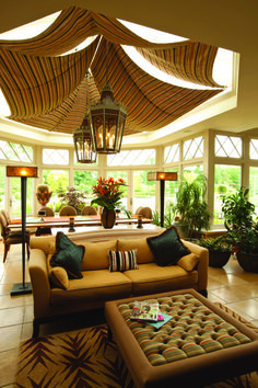 Warmth and drama in a garden room with draped blinds