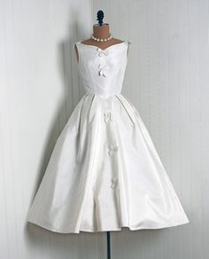 Wedding Dress: 1950's, sculpted medium-weight silk taffeta, sculpted bow-tie appliqued bodice, button-backside full circle skirt.