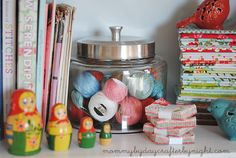 Glass jars found at HomeGoods used to store pearl cotton balls and thread! Check out more of Mommy by Day Crafter by Night's 'Sewing Storage Ideas!'