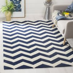 Showcasing chic chevrons in dark blue and ivory, this hand-tufted wool rug brings bold geometry to your decor. Use it to define areas in the lounge or pair it with other prints for a lived-in, layered look.