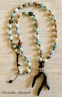 "Necklace by Alexandra Marshall featuring a Black Coral branch suspended from Matte Flower Amazonite accentuated with Air Blue Opal and Clear Crystal. 30"" -34"" long with slide knotted hand tied cotton cord. #N2611. $119."