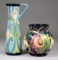 """A modern Moorcroft pottery bulbous vase decorated with """"Pomegranate"""" pattern on a dark blue ground, 5.75ins high (impressed factory mark to base and dated 2000), and a ditto jug decorated with a lily pattern in the Art Nouveau manner on a pale blue ground, 9.5ins high (impressed factory mark and dated 2001 to base"""