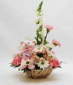 It's a Girl Bouquet  This darling baby girl arrangement is designed in a natural wicker basket using white Snapdragons, pink Carnations, white Daisies and Chrysanthemums, pink Alstroemeria and delicate Babys Breath and accented with a soft plush pink Teddy Bear. $49.95