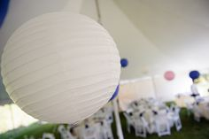 white, pink & navy blue paper lanterns decorate tented wedding reception