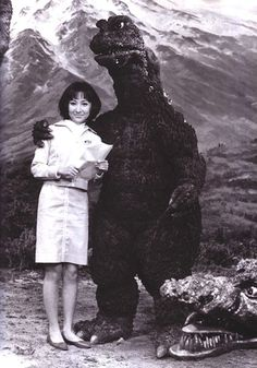 Godzilla takes time out of his busy day to pose with a fan.