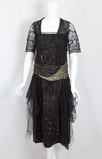 Beaded black lace dress, c.1918. Undiminished by time, this vintage treasure still weaves its seductive spell. The bodice and skirt front are embellished with jet-black beads and sequins, adding sparkle to the black-on-black design. The subtle refinement of the diaphanous design on the sleeves is beyond compare, while the gossamer delicacy of the floral motifs have a magical allure. Here is a dress for a woman whose very manner and style intimates the seductive sophistication of the evening.