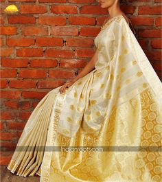 Beige tissue off-white saree featuring embossed floral zari motifs across the palla and borders by Kasavu Sarees on Indianroots.com