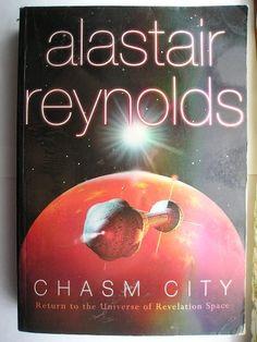 """Il romanzo """"Chasm City"""" di Alastair Reynolds è stato pubblicato per la prima volta nel 2001. Fa parte della serie della Rivelazione. Ha vinto il British Science Fiction Association award. Al momento è inedito in Italia. Immagine di copertina di Chris Moore per un'edizione britannica. Clicca per leggere una recensione di questo romanzo!"""