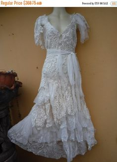 shes a wonderful romantic fantasy bohemian fairy gypsy dress that holds hours of artistic time and love...my price on etsy is a gift as these sell for hundreds more in galleries and boutiques which i supply from time to time.... in hues ivory she has been created from layers of assorted laces,crochet,netting,vintage motifs,embroidered tablecloth,beaded embroidered bridal laces,and roses she has many a tale to tell!!! adjustable shabby shoulder straps,elastic and laced up detail for a good…
