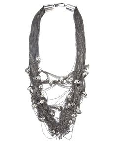 Silver multi chain necklace from Ugo Cacciatori with randomly placed skull head embellishment and hook fastening.