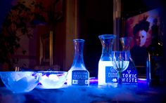 """More drinks for Halloween:  black light bar and made drinks that glow in a black light. Tonic water glows well under a black light because of the quinine in it, so I made """"Gin & Bubonic"""" and tonic water ice cubes. I also had """"Dr. Rotten's Ultimate Embalming Fluid"""" (Tampico blueberry juice and tonic water) and Toxic Waste (Mountain Dew)."""