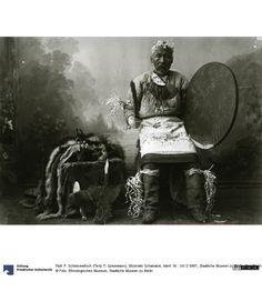 Frontalansicht eines sitzenden Schamanen , in Händen Trommel und Schlegel, neben ihm auf einem Hocker: die Krone.