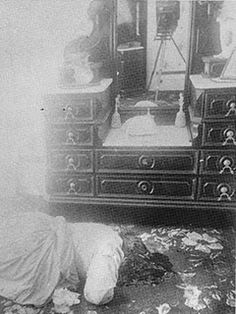 Abby Borden's body as it was found in the home...well probably as it was found. The photos weren't taken until about 3pm in the afternoon so she would have been dead for six or more hours, the crime scene completely disturbed and, for example, the bed has even been moved to take the photograph...which you can see in the mirror.