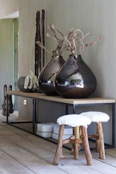 Simple timber and steel console teamed with the large metallic vases and the raw stools. Interesting mix.