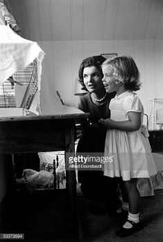 Jackie Kennedy wife of Senator and daughter Caroline watching bird in cage at home