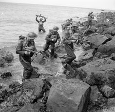 Men of Oxfordshire and Buckinghamshire Light Infantry clamber over rocks, having swum ashore during 'toughening up' exercises by the sea at Castlerock in Northern Ireland, 14 July British Armed Forces, British Soldier, British Army, Commonwealth, British Commandos, Marine Commandos, Ww2 Photos, Royal Marines, War Photography