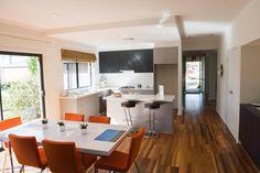 This orange and white decor goes lovely with the dark colored hardwood floors  #hardwoodfloors #kitchenremodeling