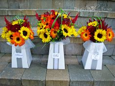 Love the multi colored sunflowers....work them in a little with the baby's breath in the flower arrangement's