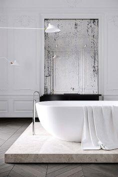 Antique Mirror with Modern Bathroom. tub on a raised platform. chevron bleached wood floors.