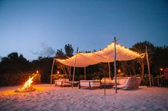 Lounge area for a beach wedding, complete with a bonfire for guests to enjoy.