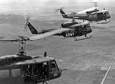 Hueys flying in close formation in preparation for an air assault. Door gunners maintain watch as the helicopters fly over Vietnam's terrain. Bell Helicopter, Military Helicopter, Military Aircraft, Vietnam War Photos, American War, American Soldiers, North Vietnam, Military Equipment, History Photos