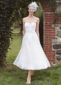 Give short and sweet a whole new meaning in this stylish strapless tea length wedding dress. Ruched bodice with inverted basque waist add texture and an appealing focal point. Full tulle skirt brings drama and a sophisticated twist. Woman: 9WG3486, $349, 16W-26W (special order only). Sizes 0-14. White available in stores. Ivory by Special Order Back zip. Dry clean only. Imported. To preserve your wedding dreams, try our Wedding Gown Preservation Kit.A gown or skirt with a hem that falls betwe...