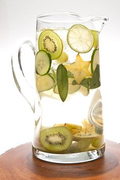 White Sangria with slices of limes, apples, cucumbers, kiwi, sage leaves star fruit and green grapes. nom!
