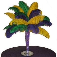 Mardi Gras themed ostrich feather centerpiece with trumpet vase and water beads. The water beads really sparkle when lit by submersible floralytes. #eventplanning, #mardigras