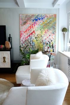 I'm not sure if those walls are faux finished or if that's grass cloth paper, but it's a gorgeous backdrop for some bright, modern, abstract art. The scale is pretty incredible in this space and the use of white furniture really allows this piece of art to kill it.