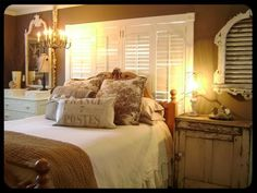 When the only option is to put the bed in front of the windows, hang shutters!  Not only do they offer privacy, but they also act as a headboard.: