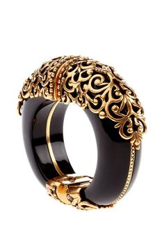 Oscar de la Renta Spring 2013. This big black beast of a bracelet is perfectly escorted by the delicate and feminine touch of gold filigree design appliques.