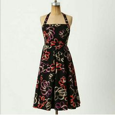 Anthropologie Halter Dress Rockabilly By Girls From Savoy. Black with purple red and tab design. Size 2.  100% cotton. Has black petticoat beneath with purple trim.  Preowned but great condition!  Sides of top have elastic panels for stretch.  Straps are removable.  Zipper back with hook/eye closure at top.  The hook is a little loose and slightly bent open .needs to be sewn tighter if desired. Anthropologie Dresses
