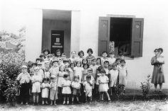 Niños puertorriqueños posando ante la camara en su descanso de merienda en el exterior de una escuela del pueblo de Aibonito,Puerto Rico,,notese el profesor en la ventana,con colbata,,año, (1930).