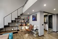 To the right, white walls offer a respite for wardrobes and bookshelves, which…