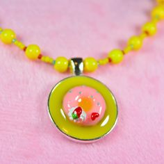 Embrace your playful side with a bright yellow donut necklace. Or give it to a sweet girl. This 17-inch necklace features yellow, red and blue Czech glass beads that frame a central charm. It closes in the back with a silver lobster clasp. The silver charm features a resin frosted donut embedded in yellow resin. Kitsch doesn't get much cuter than this! $20. Click to buy now from #SmallestPlanet.