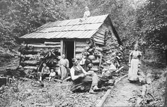 Mountain cabin taken by Wayne County, WV  photographer Thomas Luther. There is no better photo to illustrate the harshness and beauty of mountain life. So many things near and dear to mountaineers are shown in this photo - family, farming, hunting, dogs, and even banjo picking (note the kid behind the barrel of the gun).   From Doris Miller Papers, Marshall University Special Collections