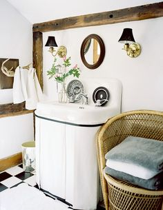 Bathroom Photo - A pair of brass sconces and an oval mirror above a skirted sink