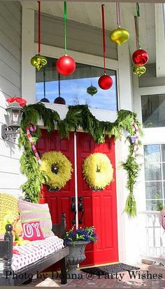 Love the ornaments hanging from porch ceiling..................A Whole Bunch Of Christmas Porch Decorating Ideas - Christmas Decorating -