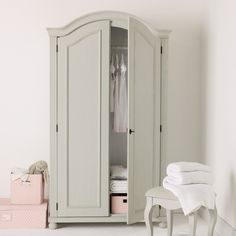 pink storage baskets, and a gray armoire.