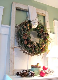 cute inspiration pinecone wreath on an old window, looks like it's on greenery with nuts in the wreath, too.  no tut