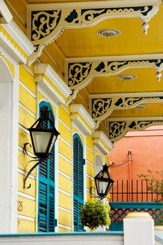 Louisiana Architecture. Gingerbread brackets. Bold yellow and blue painted double shotgun house - porch