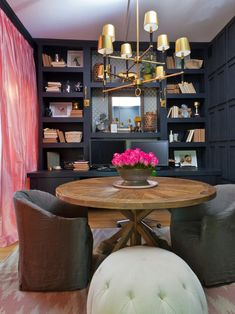 Genevieve revamps a bland home office by adding built-in bookshelves, floor-to-ceiling draperies, a luxe chandelier and a round worktable that can also serve as a meeting spot.