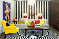 QIDA It's all about the intensity of colour and pattern in this lounge room by the Queensland Interior Decorators Association (QIDA).The strength of the primary colour combination of yellow, red and blue is further enhanced by a black and white striped wall and rug – a striking combination which doesn't take itself too seriously. A playful canvas and plenty of glass accessories complete this fun and artistic space.
