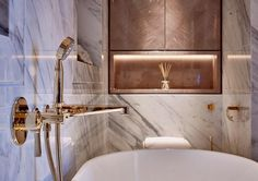 Bathroom brass details and niche wall, surrounded by marble.
